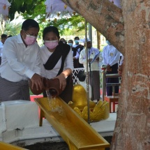 State Administration Council Chairman Commander-in-Chief of Defence Services Senior General Min Aung Hlaing, wife Daw Kyu Kyu Hla, Council members and wives pour water at banyan tree on fullmoon day of Kason